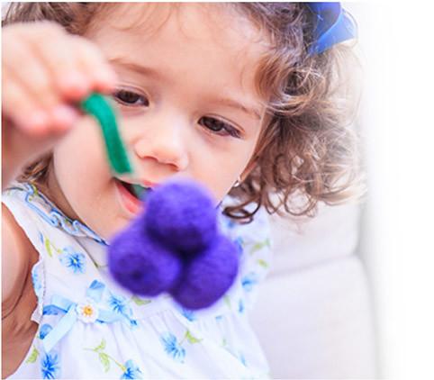 Menina segurando uvinha de crochet
