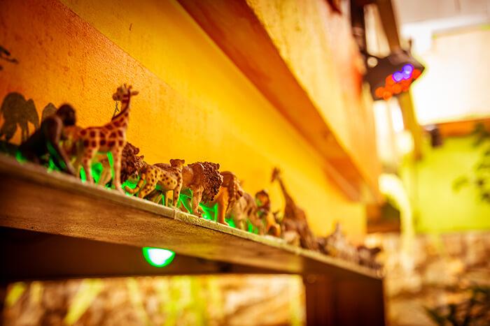 Foto do detalhes da decoração do espaço: mini animais caminham no horizonte sobre a mesa do bolo.