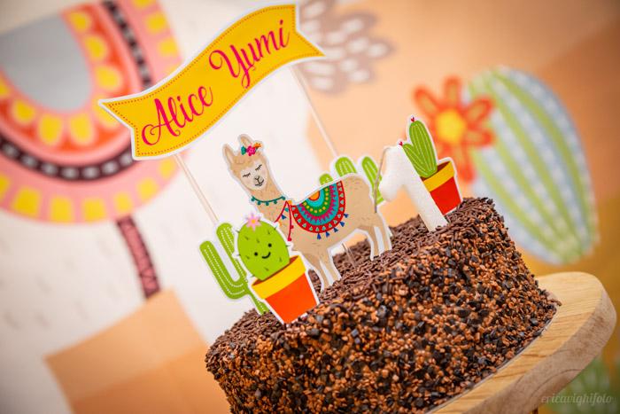Bolo de chocolate com toppers de llama e cactus e o nome da aniversariante
