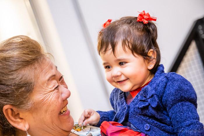 foto de festa: bebê sorrindo no colo da vovó