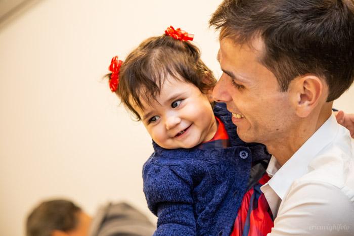 foto de festa: bebê sorrindo no colo do papai