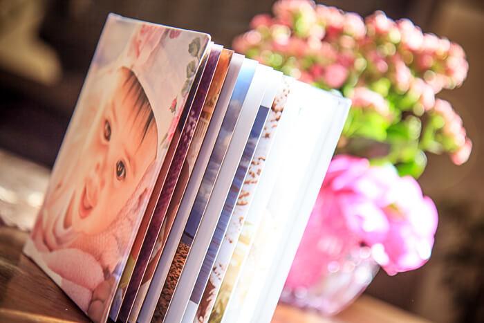Imagem de album quadradinho em perspectiva com bebê na capa e um vaso de flores ao fundo