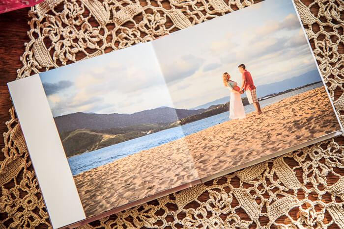 Imagerm de album de ensaio de gravidez com foto do casal na praia, ao por do sol.